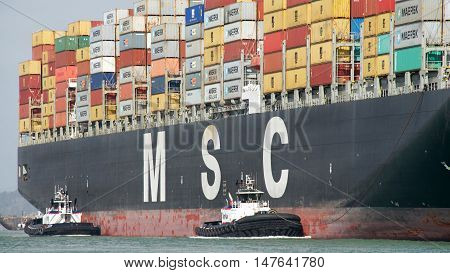 Oakland CA - September 12 2016: Multiple tugboats assist Cargo Ship MSC ARIANE to manuever into the Port of Oakland. A tugboat maneuvers vessels by pushing or towing them.