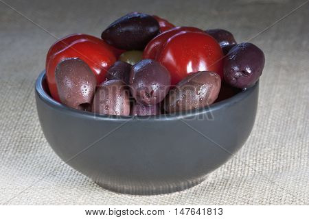 tomatoes and olives in a black bowl onthe table