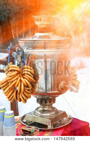 shrovtide simblols samovar with boiled water and bagels outdoor close up photo on winter snowy background