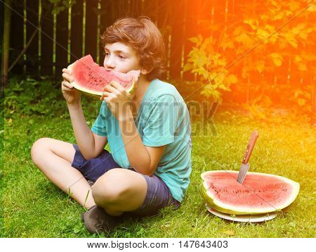 teenage handsome boy eating water melon grimacing close up portrait on the summer sunny background