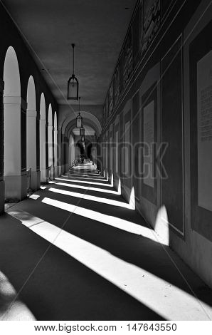 Munich, Germany - April 25, 2014: Long Arcade in Munich, Germany. Classical gallery with contrasting geometric shadows in perspective. Black and white.