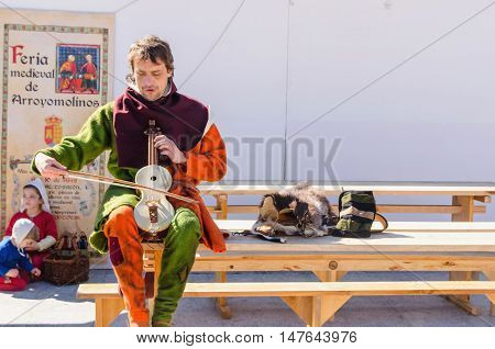 ARROYOMOLINOS MADRID SPAIN - APRIL 9 2016: man in colorful clothes plays rebec and sings in a medieval fair in Arroyomolinos Madrid Spain