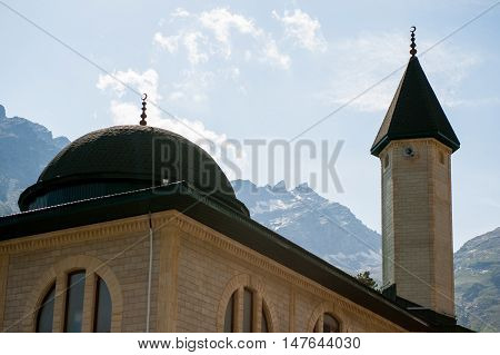 mosque on the background of snowy mountains and sky