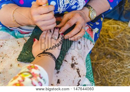 Woman Applying Henna Tattoo