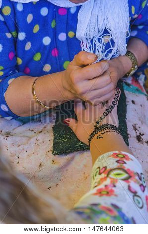 Woman Applying Henna To Make Mehndi