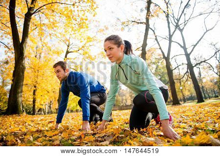 Young couple in ready position prepared for running in autumn nature