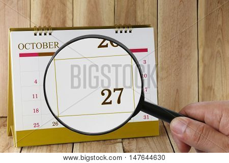 Magnifying glass in hand on calendar you can look Twenty-seven date of monthFocus number Twenty-seven in OctoberConcept in business and meetings.