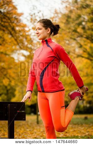 Young woman stretching her leg at bench before jogging in autumn nature