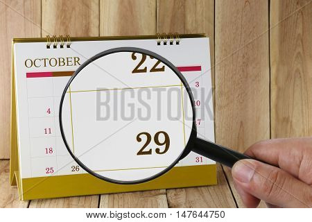 Magnifying glass in hand on calendar you can look Twenty-nine date of monthFocus number Twenty-nine in OctoberConcept in business and meetings.