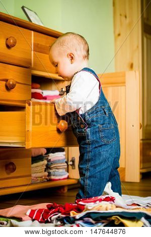 Baby throws out clothes from wooden furniture at home
