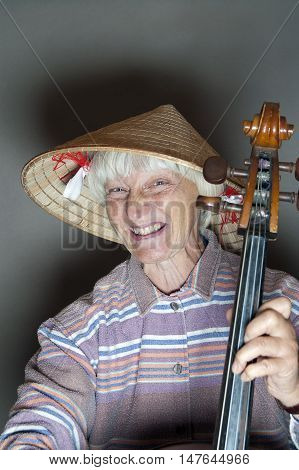 Senior female musician wearing wicker hat and playing cello emotional studio portrait