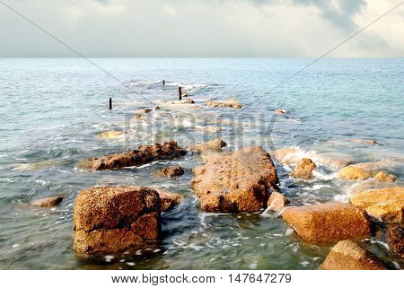 view of calm sea and stones in the morning