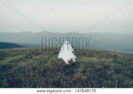 White ghost flying on meadow outdoor. Man in costume of Halloween ghost