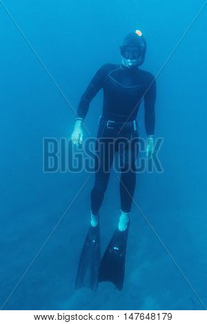 Underwater image of young man in dive suit and mask with flippers diver in full-length
