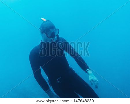 Underwater image of young man in dive suit and mask with snorkel