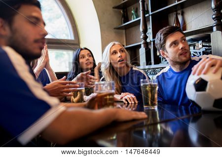 people, leisure and sport concept - happy friends or football fans drinking beer and watching soccer game or match at bar or pub