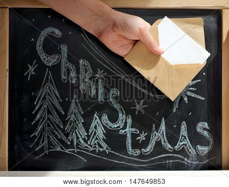 Hand with an envelope on the background of Christmas greetings on the blackboard / postman brings good news