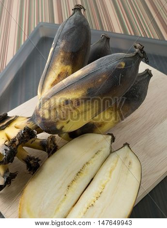 Fruits Bunch of Black Rotten Wild Banana Asian Banana or Cultivated Banana on A Wooden Cutting Board.