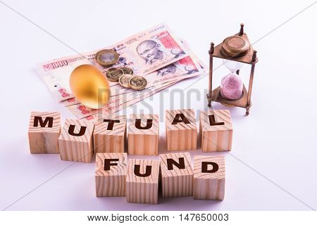indian currency notes with coins and golden egg along with antique sand clock and wooden blocks with MUTUAL FUNDS written over it