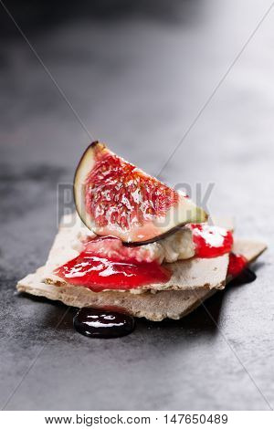 Appetizer canape with fig jam and cheese on a small loaf of bread closeup selective focus