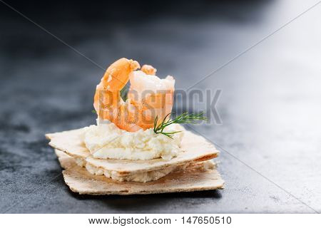 Appetizer canape with shrimp cheese and dill on a small loaf of bread closeup