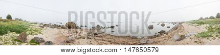 Rocky beach and morning fog in summer. Sea mist coast forest seaside natural environment. Shore in Koipsi Island Estonia Europe. 360 degrees panorama.