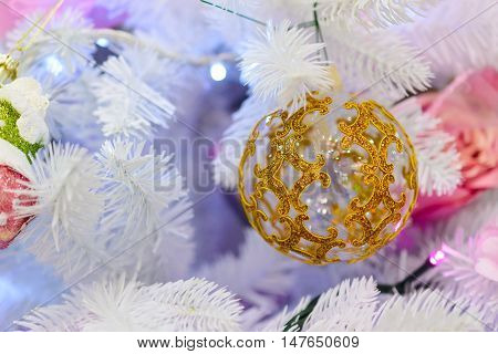 Christmas decorations on artificial fir. Christmas decorations on artificial fir. Christmas teddy glass ball with patterns.