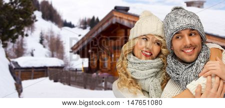 people, christmas, holidays and season concept - happy family couple in winter clothes hugging over wooden country house and snow background