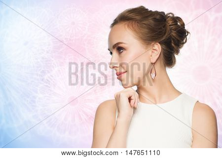 jewelry, luxury, wedding and people concept - smiling woman in white dress wearing pearl earrings over rose quartz and serenity pattern background