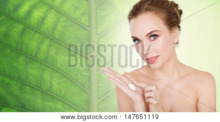 beauty, people, skincare and cosmetics concept - happy young woman with moisturizing cream on hand over natural green leaf background