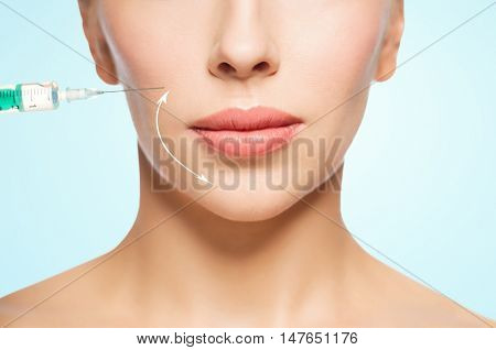 people, cosmetology, plastic surgery, anti-aging and beauty concept - beautiful young woman face and syringe making injection over blue background