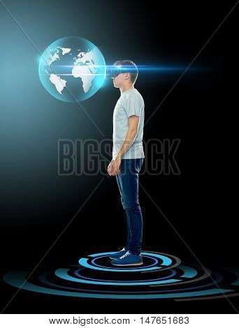 3d technology, gaming, augmented reality, cyberspace and people concept - happy young man with virtual reality headset or 3d glasses looking at earth globe hologram over black background