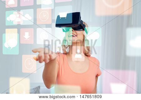 technology, augmented reality, multimedia and people concept - happy young woman with virtual headset or 3d glasses looking at menu icons