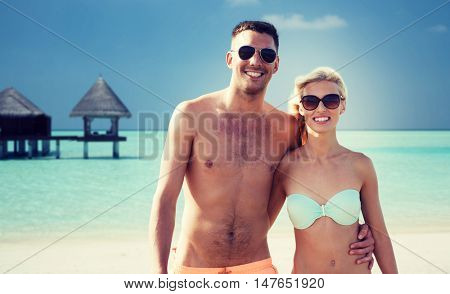 love, travel, tourism, summer and people concept - smiling couple on vacation in swimwear and sunglasses hugging over beach with bungalow background