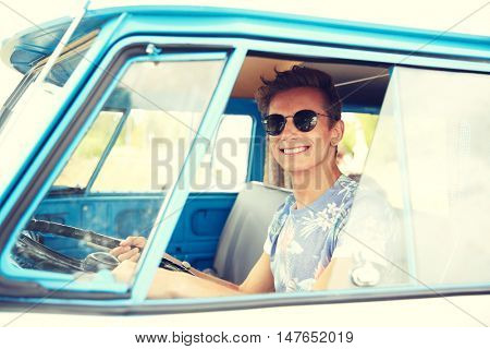 summer holidays, road trip, vacation, travel and people concept - smiling young hippie man driving in minivan car