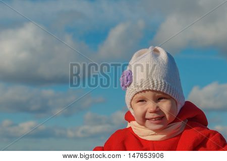baby in warm clothes laughs against the sky with clouds