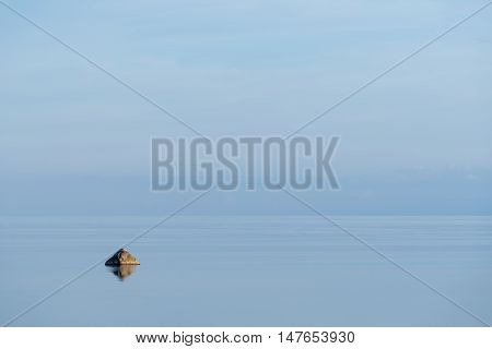 Evening sunlight on the coast blue sky reflection on the water. Beach in summer. Seaside natural environment background. Shore in Osmussaar Island Nature Reserve in Estonia National Park in Europe
