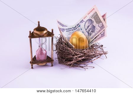 hourglass with Golden egg and indian money or indian currency note in a real nest. Shallow focus.