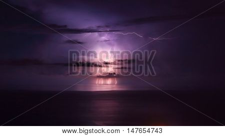 Purple lightning over the sea, powerful thunderbolt, amazing night landscape, stormy weather in the sea, beautiful natural wallpaper