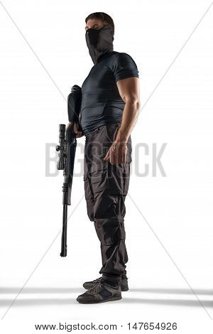 Standing soldier in headgear and black military uniform holding rifle isolated on white background