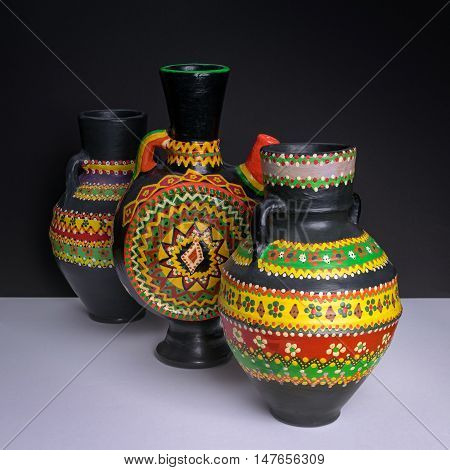 Still life of three black decorated handcrafted pottery vases on background of white table and black wall