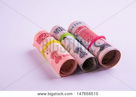 Roll of indian rupees with rubber band isolated on white background