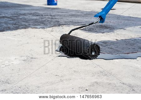 Worker covered surface bitumen primer for improving adhesion during surfacing rolled waterproofing during the installation of isolation on industrial or household objects