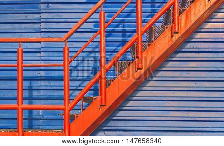 part of red fire escape on the blue wall.