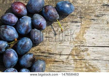 Fresh plums on the rustic wooden background