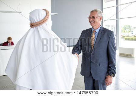 Mature director of company handshake with Arabian partner