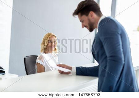 Young pretty female receptionist look at handsome businessman at check desk