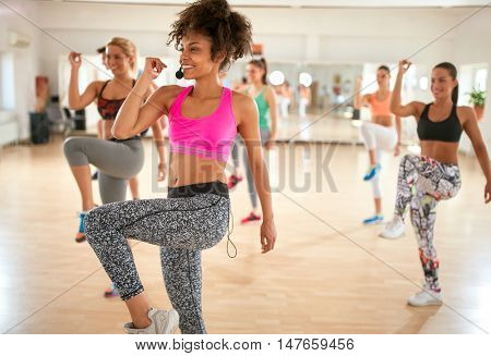 Young black girl leads exercisers in group at gym