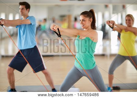 Cute girl exercising with resistant rubber in fitness class