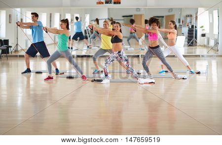 Fitness practicing group uses resistant rubber in gym
